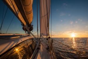 Coucher de soleil sous le vent d'un voilier se déhalant par petite brise.