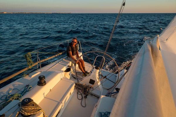 Au large de Marsala (Sicile), le patron à la barre. Fin de journée, un ris, short et manches courtes. La Méditerranée en fin de saison réserve comme cela quelques petits moments de grâce.