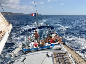 Un équipage heureux dans le cokpit d'un voilier, sous le soleil et sous une bonne brise, avec la côte de la Corse occidentale en arrière plan.