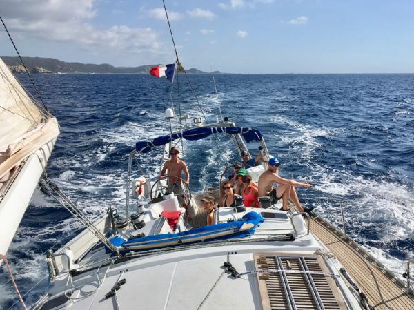 A happy crew in the cokpit of a sailboat, under the sun and under a good breeze, with the coast of West Corsica in the background.